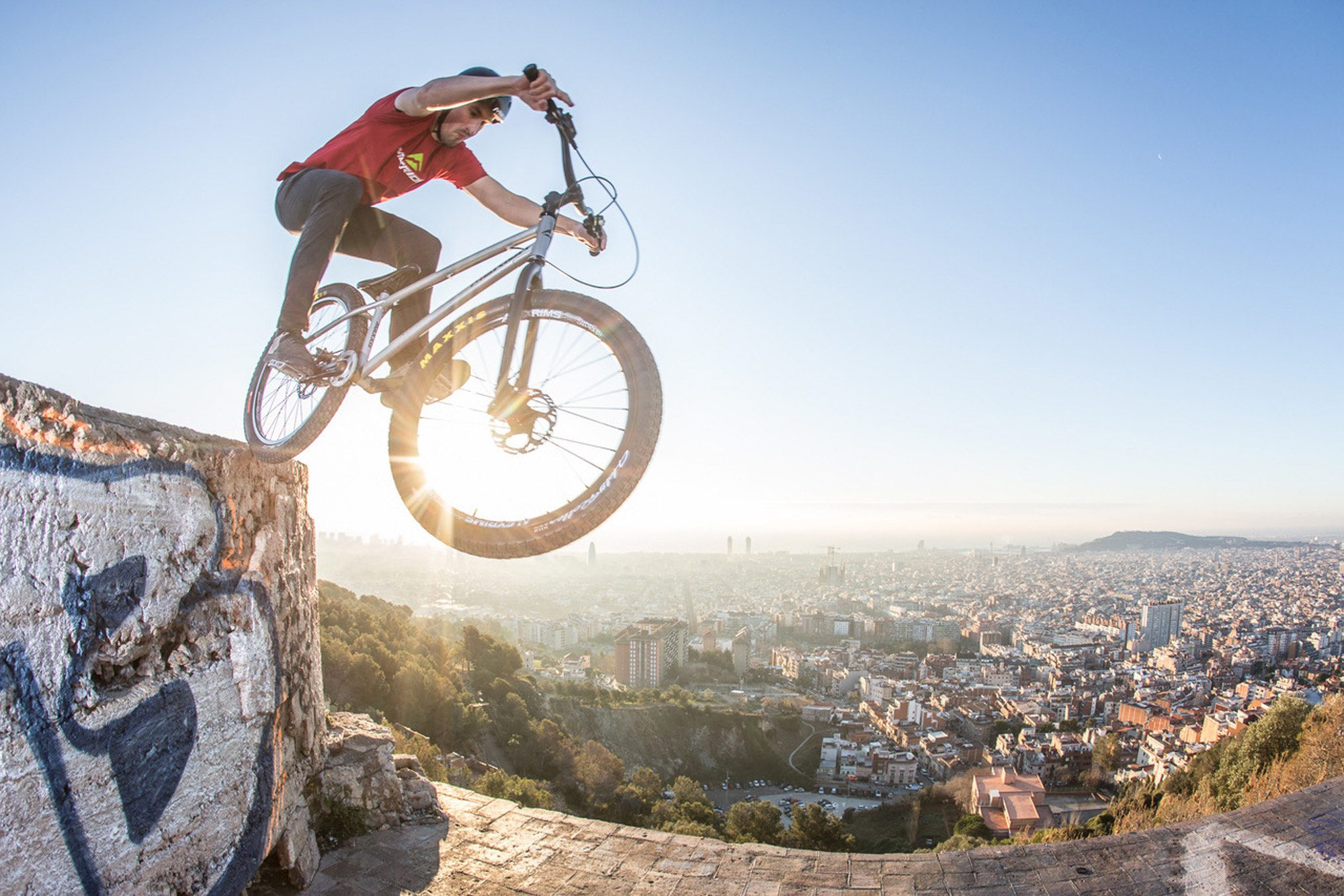 Dominik Raab steht mit dem Hinterrad auf einer Mauer über den Dächern von Barcelona