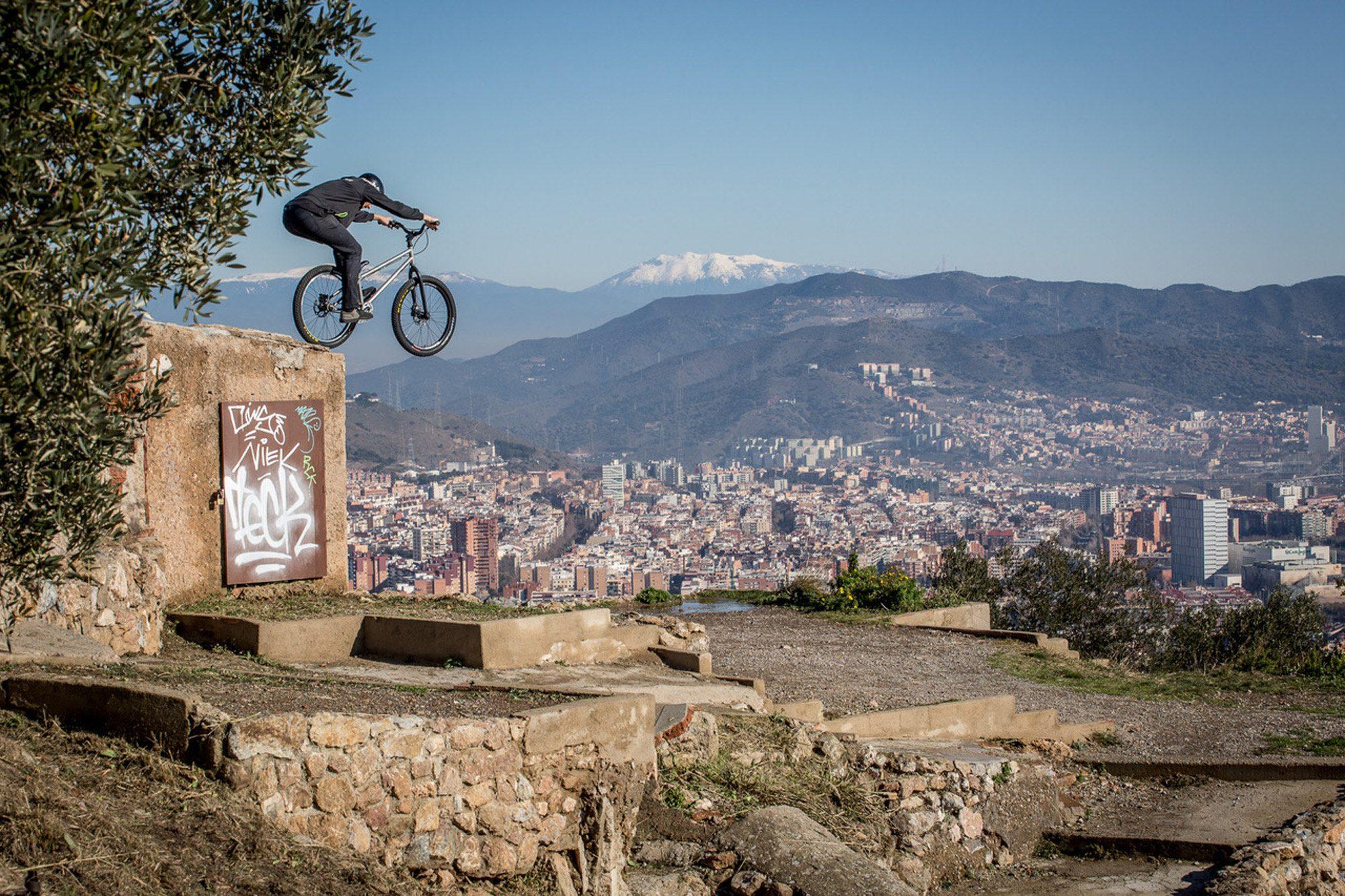 Dominik Raab springt von einer Mauer runter und im Hintergrund sieht man Barcelona und Berge