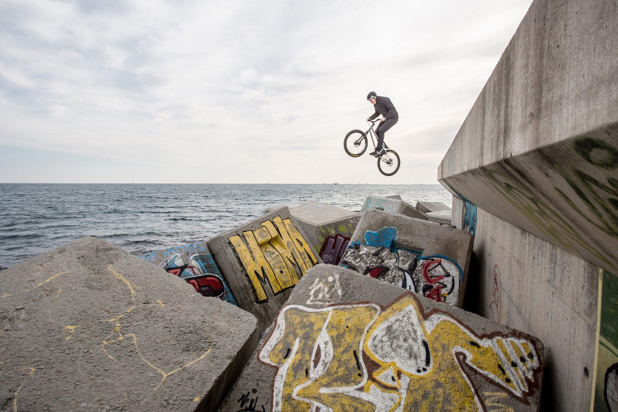 Dominik Raab springt auf Betonwürfel neben dem Meer