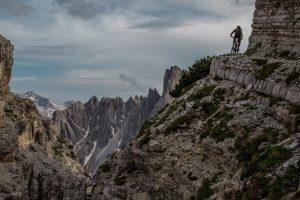 Dominik Raab fährt einen Trail und im Hintergrund sieht man viele Berge