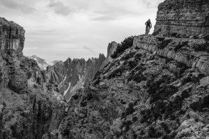 Dominik Raab fährt um eine Kurve und im Hintergrund sieht man Berggipfel