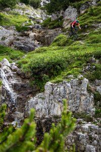 Dominik Raab fährt mit dem Fahrrad auf einem Weg neben einem Wasserfall