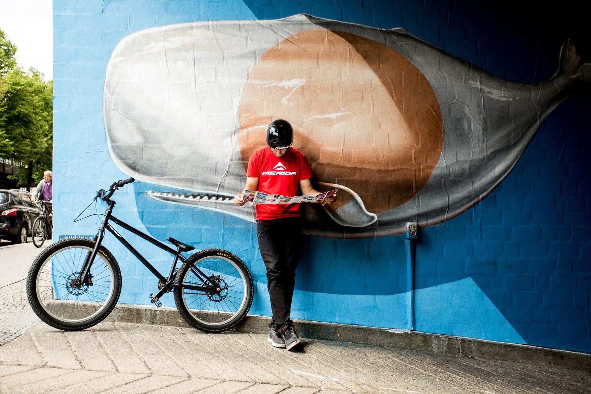 Dominik Raab lehnt an einer Wand und studiert den Stadtplan