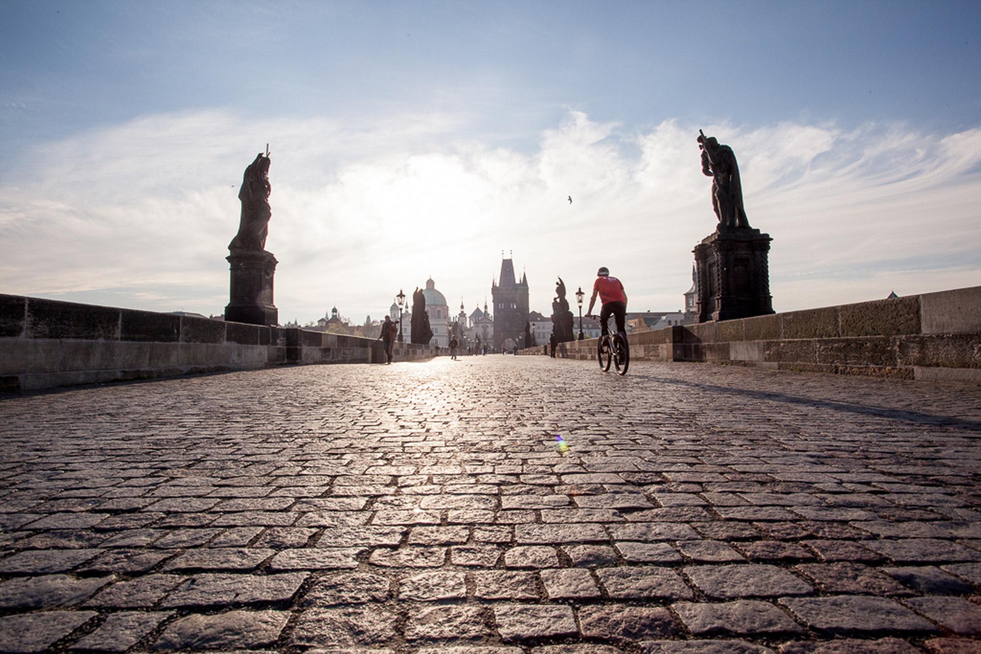 Dominik Raab fährt mit seinem Fahrrad auf der bekannten Karlsbrücke