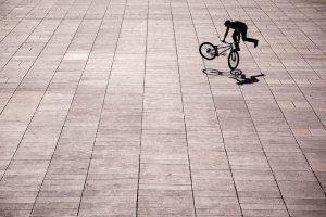 Dominik Raab macht Tricks auf dem Trialbike auf einem großen Platz in Prag