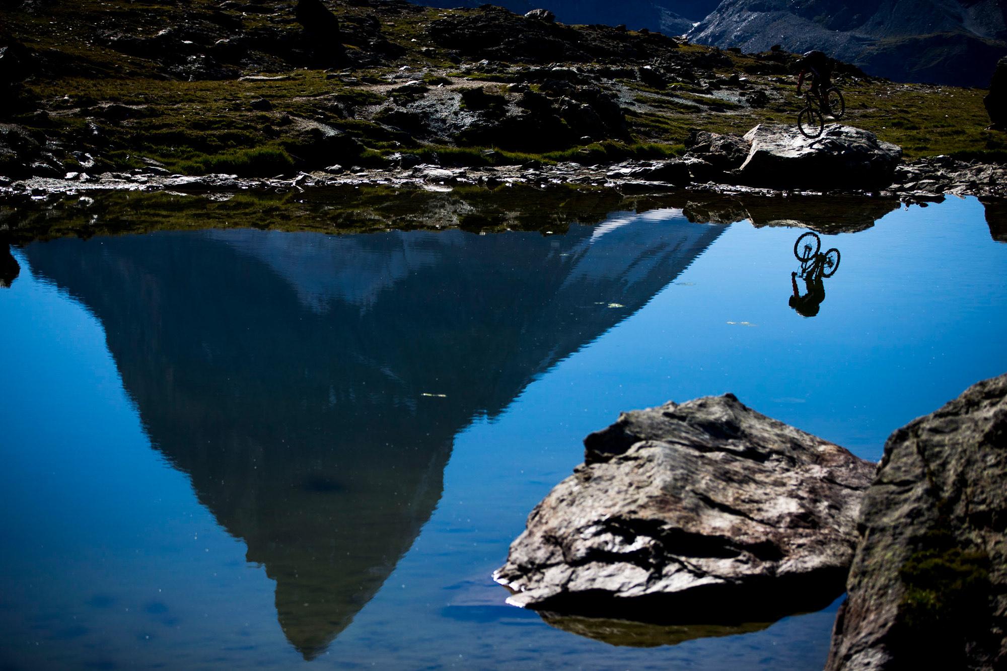 Dominik springt auf dem Vorderrad auf einem Felsen und dahinter ist das Matterhorn zu sehen