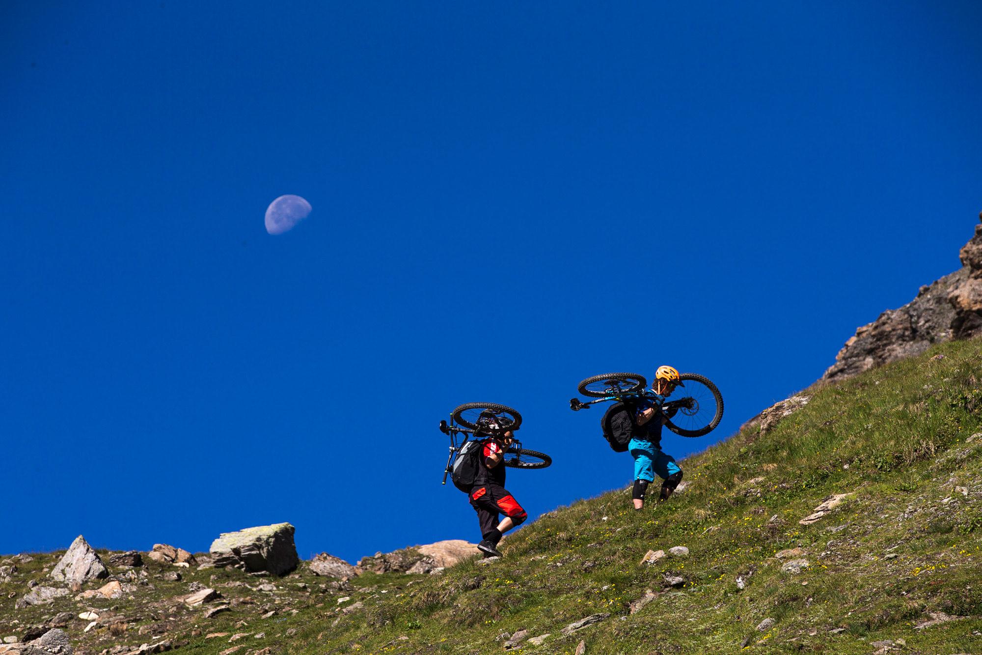 Dominik Raab und Alban Aubert tragen ihre Bikes auf einen Berg hoch