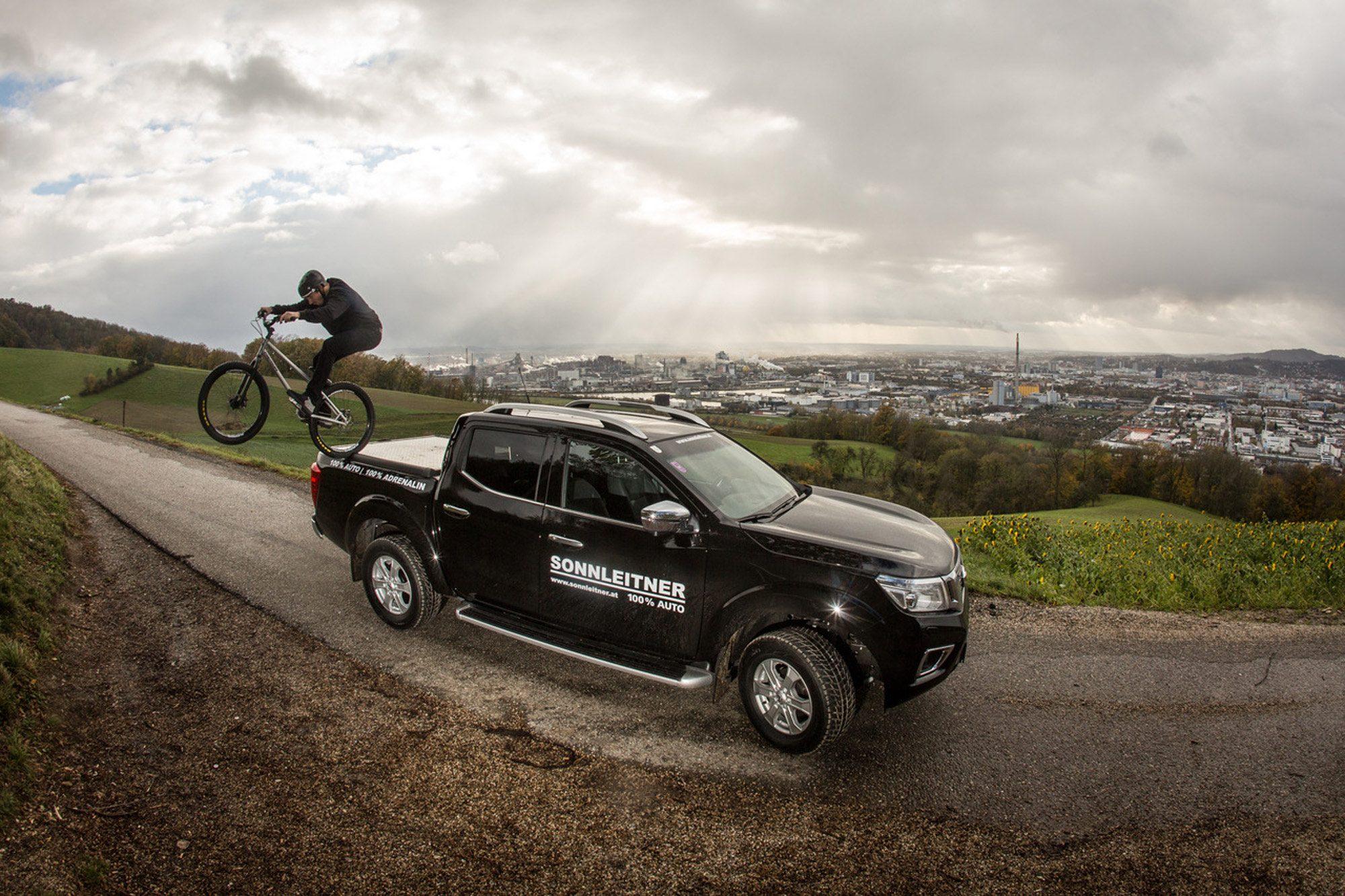 Dominik Raab bei einem Sprung von seinem Nissan Navara mit Blick über Linz