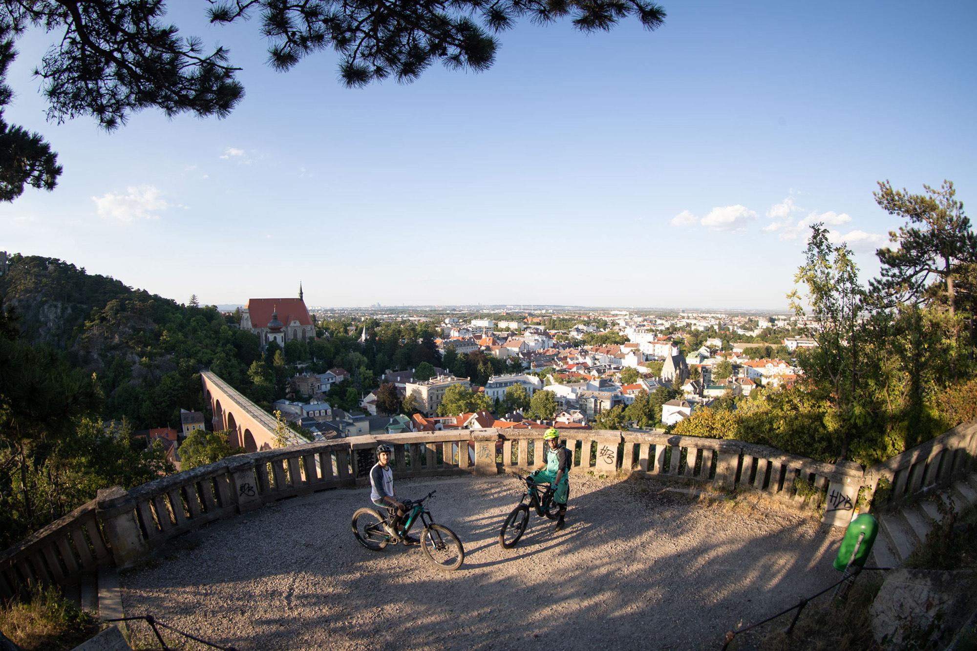 Dominik und Alban sitzen auf ihrem Bike und man sieht die Dächer Wiens im Hintergrund