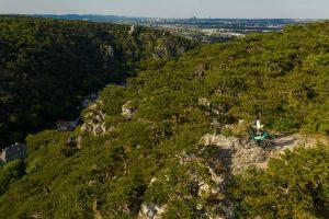 Dominik Raab steht mit seinem E-Mountainbike auf einem Berg und man sieht Wien im Hintergrund