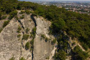 Dominik Raab und Alban Aubert fahren einen schönen Trail entlang einer Felskante und im Hintergrund sieht man die Stadt Wien