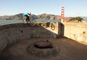 Dominik Raab springt von einer Mauer vor der Golden Gate Bridge