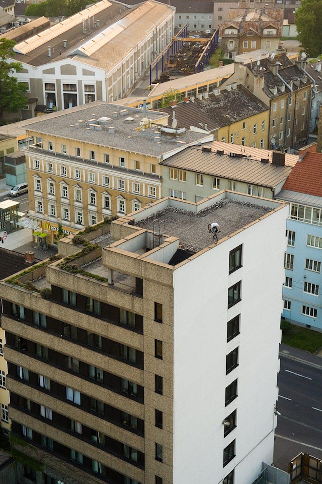 Dominik Raab steht am Vorderrad auf der Kante eienr Mauer auf einem Hochhaus